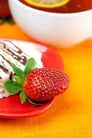 lemon tea, cake and strawberries lying on the orange fabric Stock Photo - 8671918