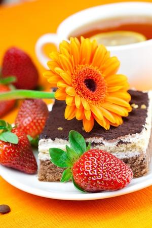 gerbera, lemon tea, cake and strawberries lying on the orange fabric photo