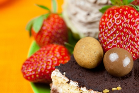 cake, chocolates and the strawberries on the orange fabric photo