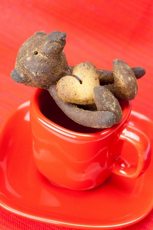 teddy bear  handmade and cookie  in the form of heart  in a cup  on a red background photo