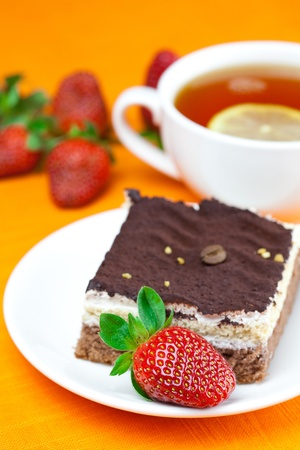 lemon tea, cake and strawberries lying on the orange fabric photo