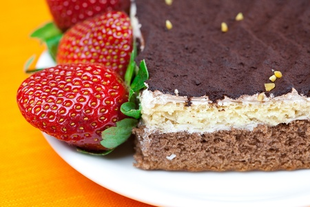 cake on a plate and strawberries lying on the orange fabric Stock Photo - 8721500