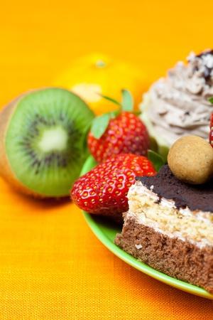 cake, chocolate candy, tangerine, kiwi and strawberries on the orange fabric photo