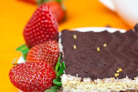 cake on a plate and strawberries lying on the orange fabric Stock Photo - 8721621
