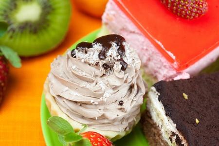 kiwi,cake and strawberries lying on the orange fabric photo