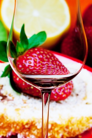 conceptually illuminated glass of wine on the background of strawberries photo