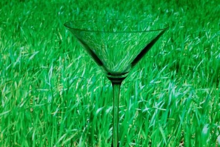 conceptually: conceptually illuminated martini glass on a background of green grass