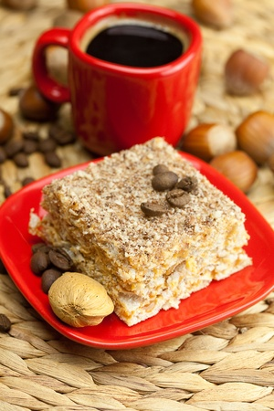 hazelnut: cake on a plate, nuts and a cup of coffee on a wicker mat Stock Photo