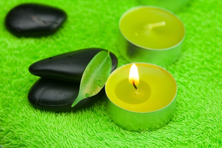 burning candle and spa black stones lying on the towel photo
