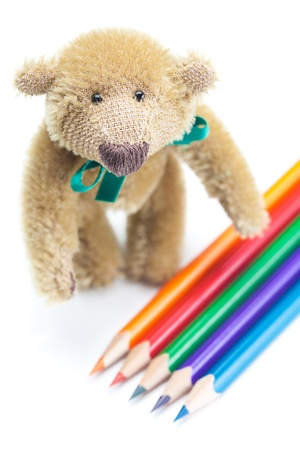 Teddy Bear  and colored pencils isolated on white photo