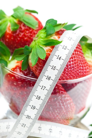 big juicy red ripe strawberries in a glass bowl and measure tape isolated on white photo