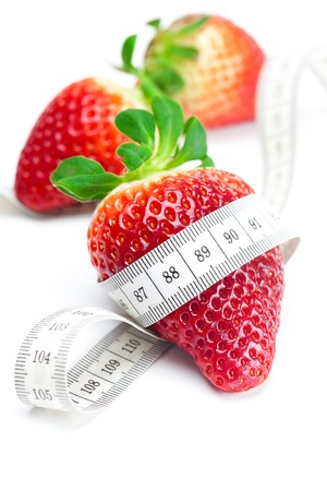 big juicy red ripe strawberries and measure tape isolated on white