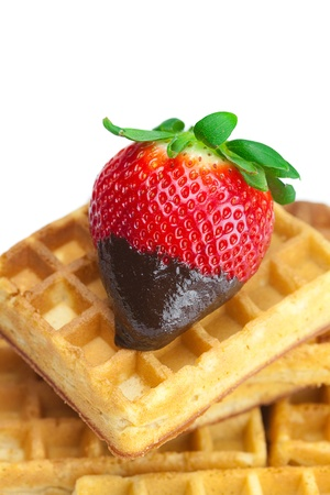 big juicy ripe strawberries in chocolate and waffles isolated on white photo