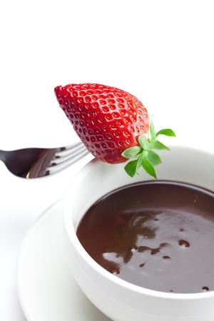 melted chocolate in a cup, fork and strawberries isolated on white photo