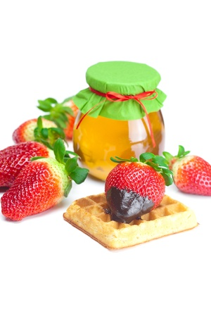big juicy ripe strawberries in chocolate, a jar of honey and waffles isolated on white photo