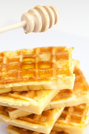 delicious Belgian waffles and stick to honey isolated on white photo