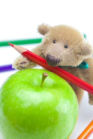 teddy bear, apple  and colored pencils isolated on white photo