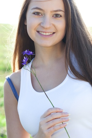 portrait of a beautiful young woman with flower  outdoor photo