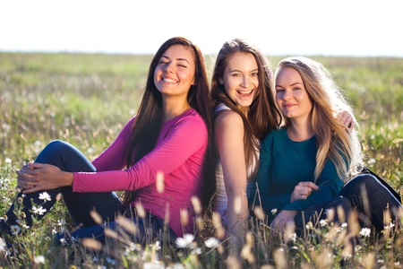 three young beautiful woman sitting in a field on the  sky background  photo
