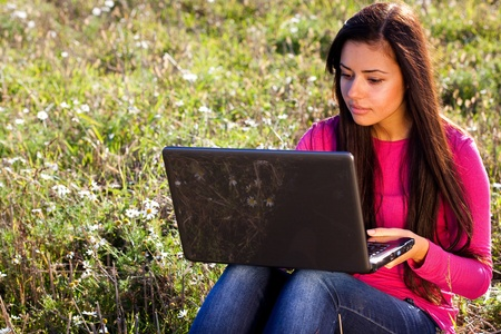 young beautiful woman with a laptop sitting in the field on sky background  photo