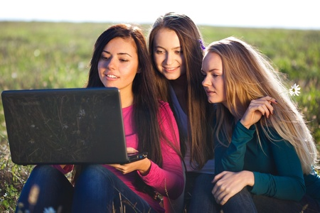 three young beautiful woman with a laptop sitting in the field on sky background  photo