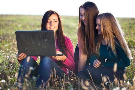 three young beautiful woman with a laptop sitting in the field on sky background  Stock Photo - 9528164