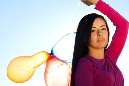 young beautiful woman with balloons into the field against the sky photo