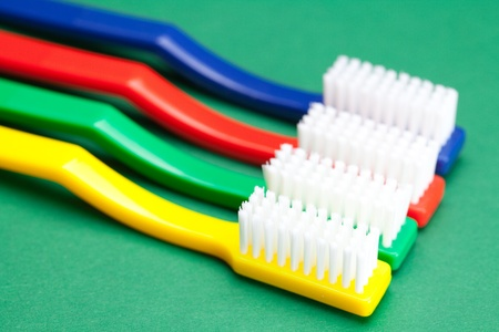 colored toothbrush on a green background photo