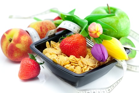 strawberry, peach, apple, kiwi fruit, tulips and flakes in a bowl isolated on white photo