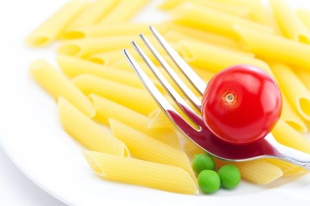 tomatoes, peas, pasta and fork on a plate isolated on white Stock Photo - 9662874