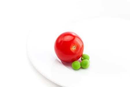 tomato and peas on a plate isolated on white photo