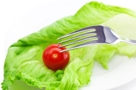 tomato and lettuce with a fork on a plate isolated on white photo