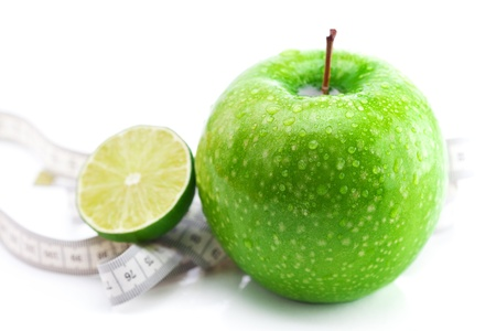 apple,lime and measure tape isolated on white