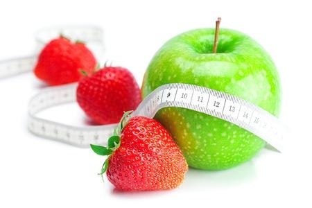 nutrici�n: grandes jugosas fresas maduras rojos, cinta de medida y apple aislados en blanco Foto de archivo