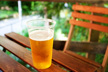 glass of beer standing on a wooden table Stock Photo - 9737432