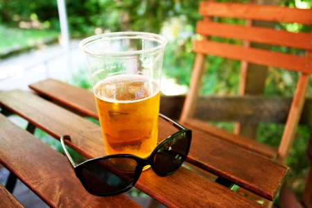 glass of beer and sunglasses standing on a wooden table photo