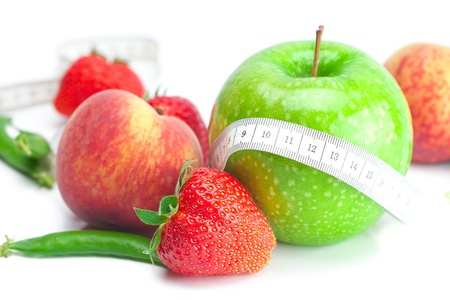 big juicy red ripe strawberries,apple,peas,peach and measure tape isolated on white Stock Photo