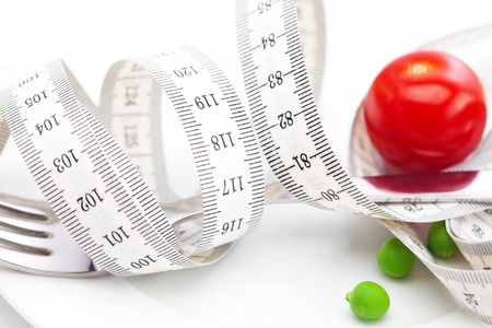 tomato,fork ,peas and measure tape on a plate isolated on white photo