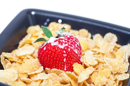 strawberry,milk and flakes in a bowl isolated on white photo