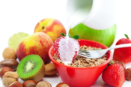 Erdbeere, Pfirsich, Apple, Kiwi, Gabel, Milch, Nüsse und Weizen in einer Schüssel, isoliert auf weiss