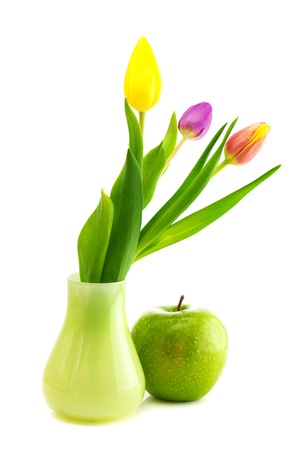 colorful tulips in vase and apple isolated on white photo