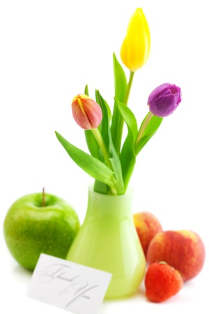 colorful tulips in vase,strawberries,apple,peach and a card signed thank you isolated on white photo