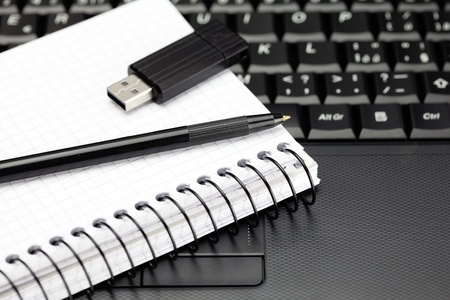 laptop keyboard, notebook, flash drive and a pencil