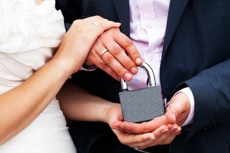 padlock with the chain in the hands of just married Stock Photo - 9737634