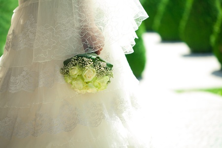 bouquet in the hands of the bride against the background of dress photo