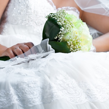 bouquet in the hands of the bride against the background of dress Stock Photo - 9995725