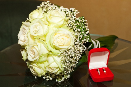 bridal bouquet and a box with the rings on a glass table photo