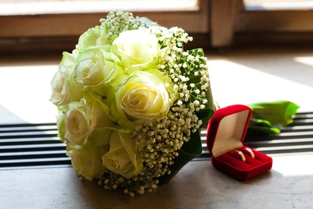 bridal bouquet and a box with the rings on the window photo