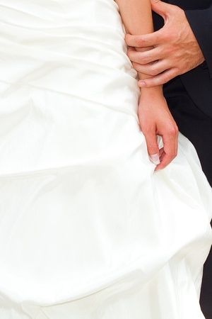 hands of the bride and groom on the background of a wedding dress