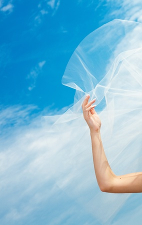 wedding dress and veil with a hand against the blue sky Stock Photo - 9995729